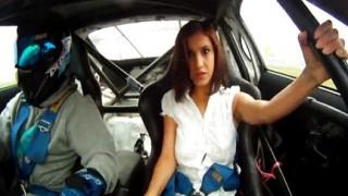 Teen tettona scollata su un'auto da corsa